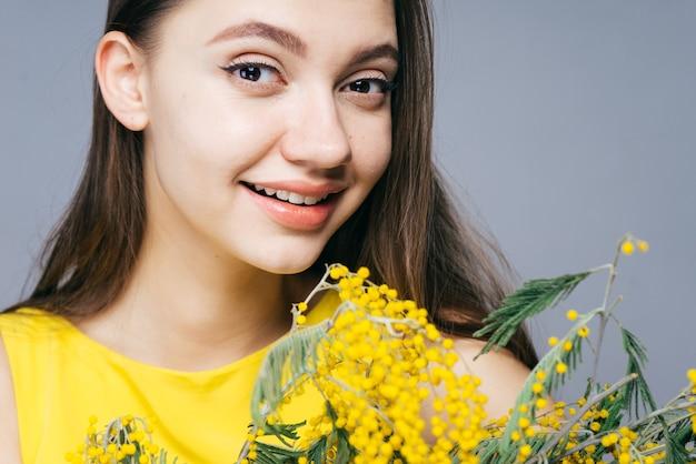 Jovem feliz em um vestido amarelo sorrindo, segurando uma mimosa amarela perfumada