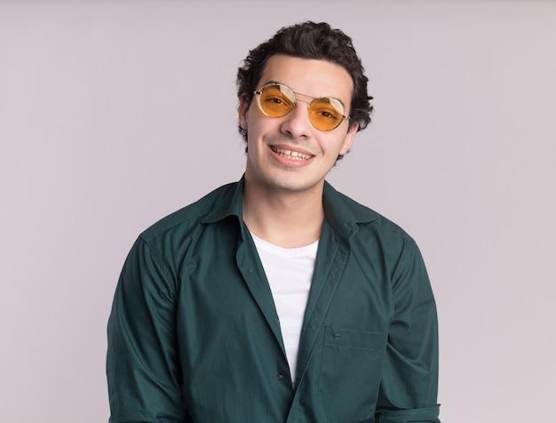 Jovem feliz em uma camisa verde usando óculos, olhando para a frente com um sorriso no rosto em pé sobre uma parede branca