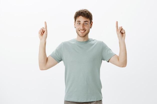 Jovem feliz encantador em uma camiseta casual, levantando o dedo indicador e apontando para cima, sorrindo amplamente como se mostrando um espaço incrível e interessante