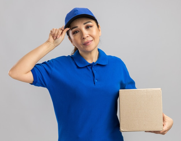 Jovem feliz entregadora de uniforme azul e boné segurando uma caixa de papelão com um sorriso no rosto em pé sobre uma parede branca