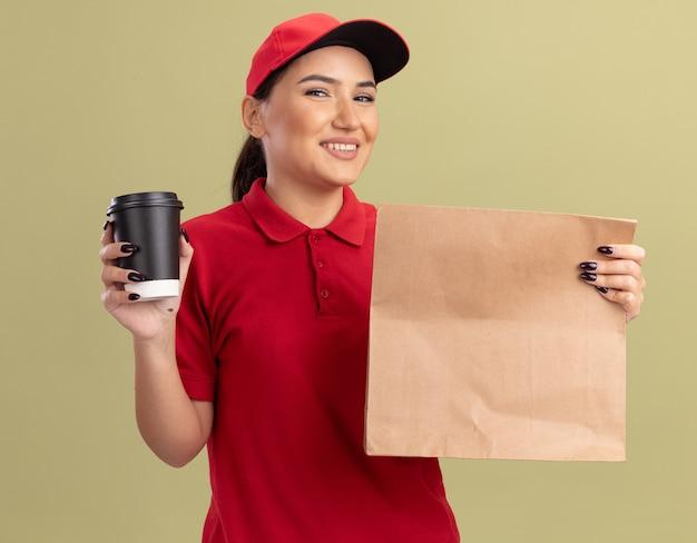 Jovem feliz entregadora de uniforme vermelho e boné segurando um pacote de papel e uma xícara de café olhando para frente com um sorriso no rosto em pé sobre a parede verde