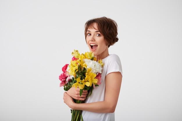 Jovem feliz espantada linda garota de cabelo curto em uma camiseta branca em branco, com a boca bem aberta e os olhos, segurando um buquê de flores coloridas, surpresa olhando para a câmera isolada sobre a parede branca.