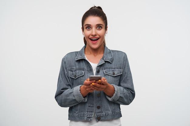 Jovem feliz espantada morena usa camiseta branca e jaquetas jeans, segura smartphone e sorri amplamente, ouvindo nova música de sua banda favorita.