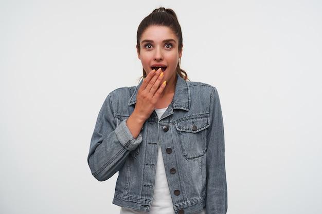 Jovem feliz espantada senhora morena em t-shirt branca e jaquetas jeans, olha para a câmera com a boca bem aberta e os olhos em expressão de surpresa, boca coberta com a palma da mão, fica sobre fundo branco.