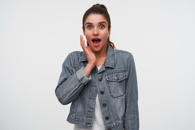 Jovem feliz espantada senhora morena em t-shirt branca e jaquetas jeans, olha para a câmera com a boca bem aberta e os olhos em expressão de surpresa, mantenha a palma da mão na bochecha, fica sobre um fundo branco.