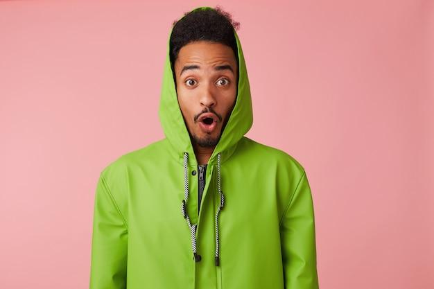 Jovem feliz espantado cara bonito afro-americano fica, parece surpreso com a boca aberta.