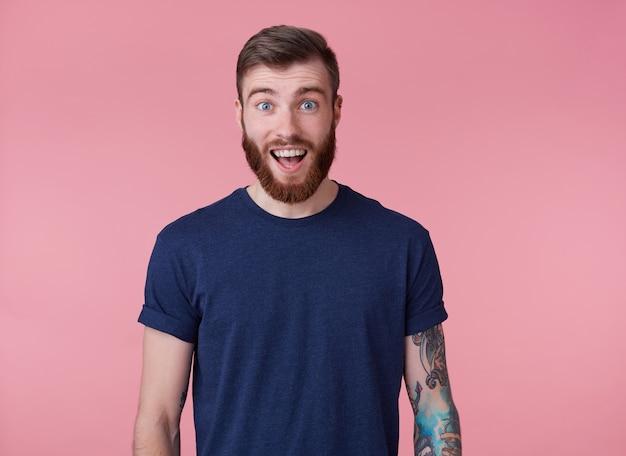 Jovem feliz espantado jovem atraente de barba vermelha com olhos azuis, vestindo uma camiseta azul, olhando para a câmera com a boca escancarada em surpresa isolada sobre fundo rosa.