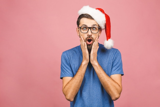 Jovem feliz expressando emoções no bom dia de natal. retrato de homem europeu espantado usa chapéu de papai noel.