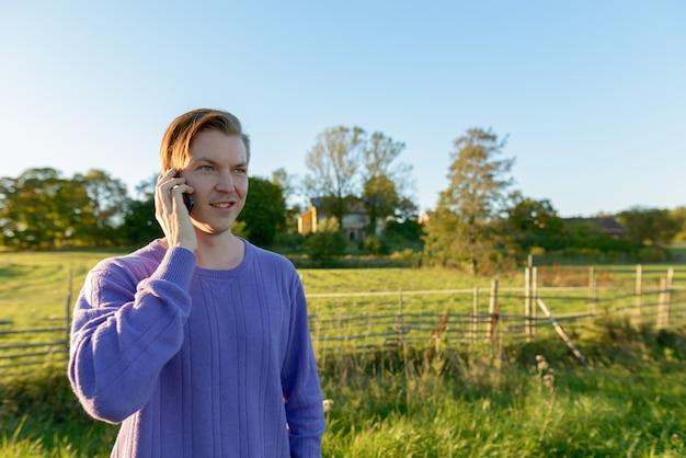 Jovem feliz falando no celular em uma planície pacífica e gramada com a natureza