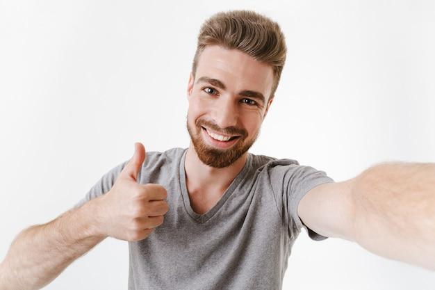 Jovem feliz faz gesto de polegares para cima tirar uma selfie.