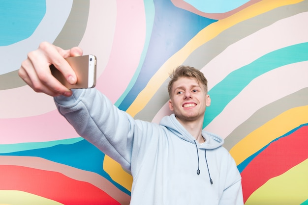 Jovem feliz faz selfie na parede abstrato colorido. sorridente adolescente é fotografado em um smartphone