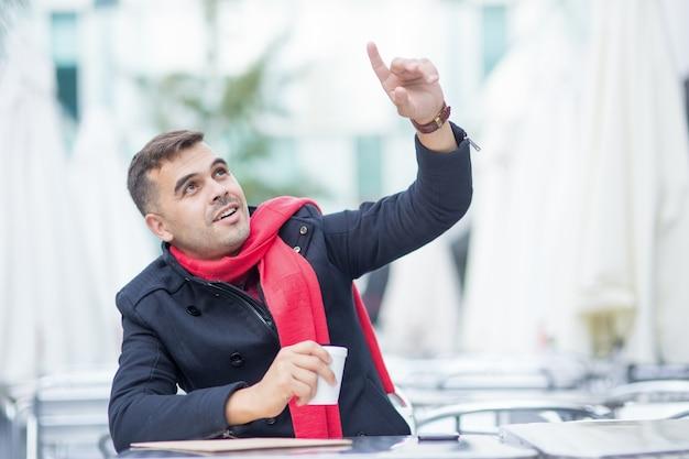 Jovem feliz fazendo ordem no café da calçada