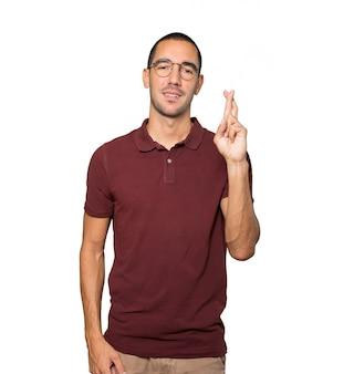 Jovem feliz fazendo um gesto de dedos cruzados