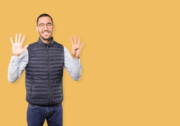 Jovem feliz fazendo um gesto de número nove com as mãos