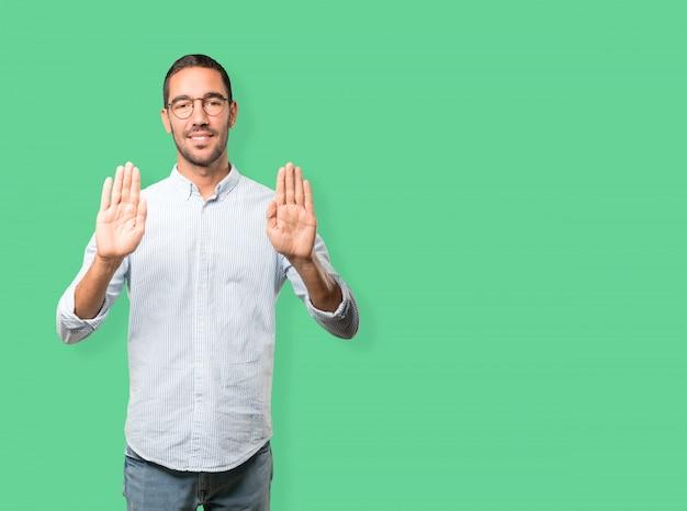 Jovem feliz fazendo um gesto de parada com a palma da mão