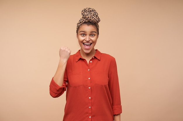 Jovem feliz feliz de cabelos castanhos com bandana olhando emocionalmente para a frente enquanto levanta a mão em um gesto de sim, isolada sobre uma parede bege