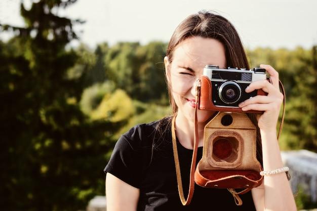 Jovem feliz fotógrafo feminino caminha no parque com câmera retro