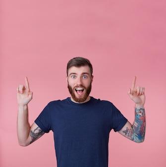 Jovem feliz gritando jovem de barba vermelha, com a boca escancarada de surpresa, quer chamar sua atenção apontando os dedos para cima para copiar o espaço isolado sobre o fundo rosa.