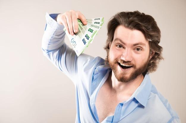 Jovem feliz homem de negócios com uma barba nas mãos de dinheiro em um fundo cinza