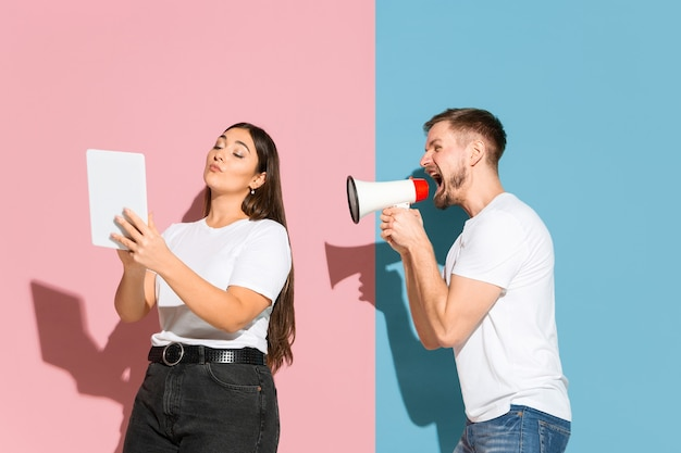 Jovem, feliz homem e mulher em roupas casuais em fundo bicolor rosa, azul.