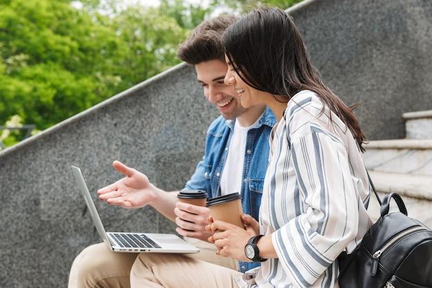 Jovem feliz incrível casal amoroso colegas de pessoas de negócios ao ar livre do lado de fora nas escadas usando o computador portátil, bebendo café.