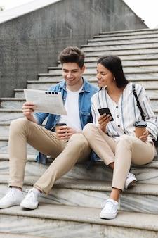 Jovem feliz incrível casal amoroso empresários colegas ao ar livre do lado de fora na escada lendo jornal, bebendo café, conversando por telefone.