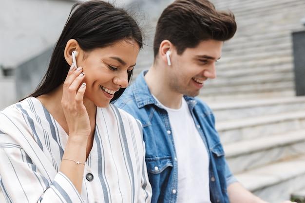Jovem feliz incrível casal amoroso pessoas de negócios colegas ao ar livre do lado de fora na escada ouvindo música com fones de ouvido.