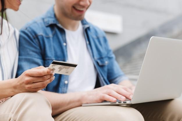 Jovem feliz incrível casal amoroso pessoas de negócios colegas ao ar livre do lado de fora usando o computador portátil, segurando o cartão de crédito.