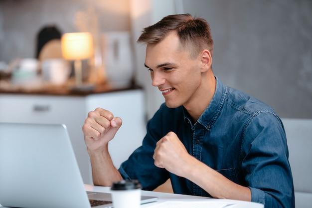 Jovem feliz lendo notícias em seu laptop pessoas e tecnologia