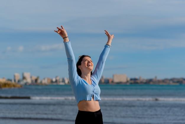 Jovem feliz levanta as mãos na beira da praia com o fundo azul do mar