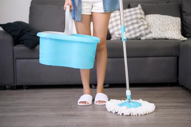 Jovem feliz limpando o chão com o esfregão na sala de estar