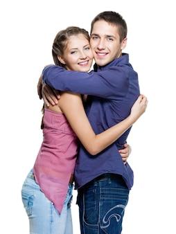 Jovem feliz lindo casal sorridente - parede branca. abraços fortes