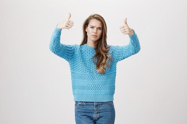 Jovem feliz mostra polegar para cima em aprovação