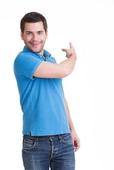 Jovem feliz mostra um dedo na lateral em casuais - isolado no branco.