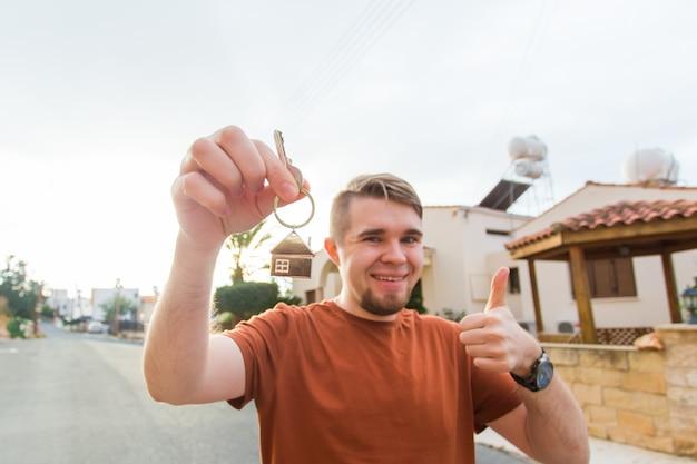 Jovem feliz mostrando a chave do conceito de imóveis e pessoas de sua nova casa