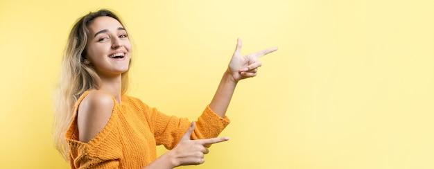 Jovem feliz mulher branca com um suéter laranja apontando os dedos para longe