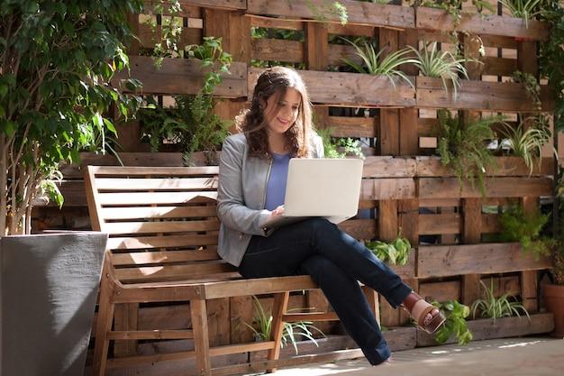 Jovem, feliz, mulher, olhar, laptop, banco, rua, plantas, fundo