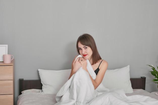 Jovem feliz na cama em casa quarto sob o cobertor.