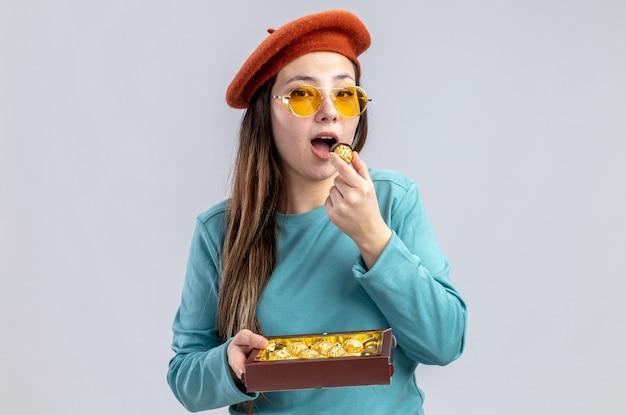 Jovem feliz no dia dos namorados usando chapéu e óculos segurando uma caixa de doces isolada no fundo branco