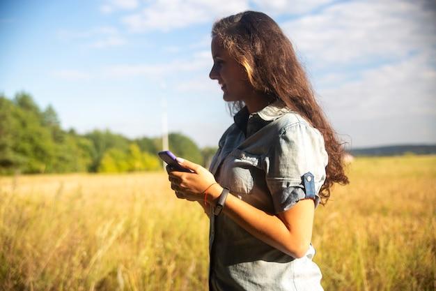 Jovem feliz olha para smartphone no fundo da natureza em dia ensolarado