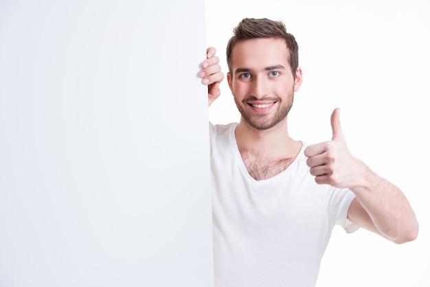 Jovem feliz olhando de um banner em branco com o polegar para cima - isolado no branco