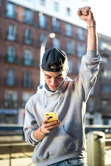 Jovem feliz olhando para o telefone animado com boas notícias online