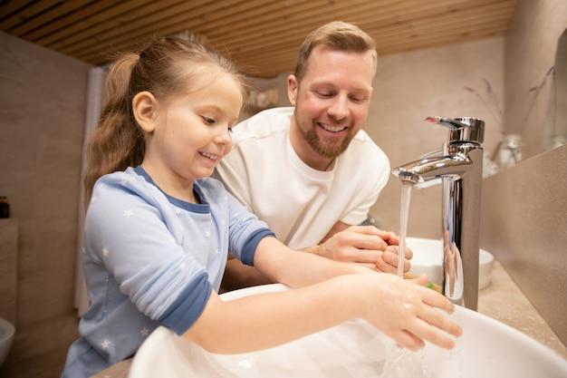 Jovem feliz olhando para sua filhinha sorridente, lavando as mãos com sabonete na pia enquanto os dois estão no banheiro