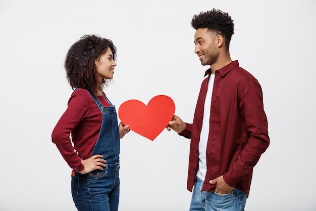Jovem, feliz, par americano africano, ligado, amor, segurando, vermelho, papel, coração