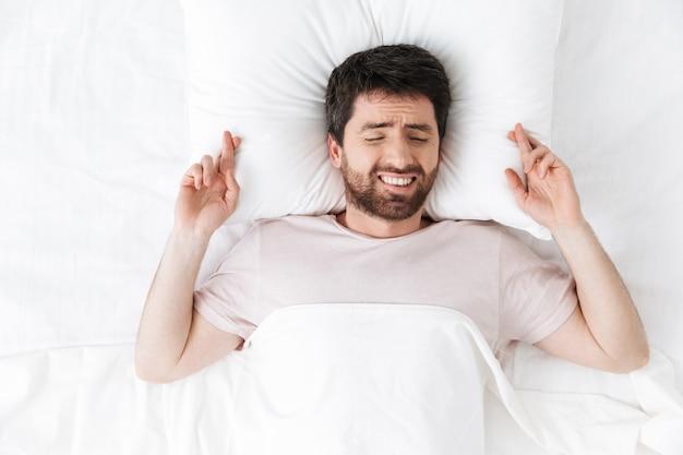 Jovem feliz pela manhã debaixo do cobertor na cama mentindo fazer um gesto esperançoso