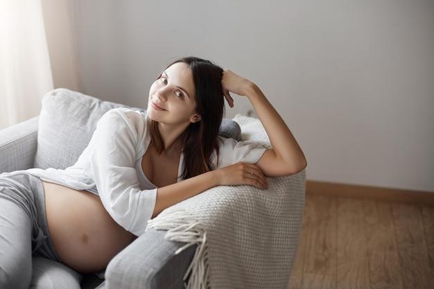 Jovem feliz por estar grávida. ficar em casa em um sofá aconchegante e aconchegante com um cobertor.