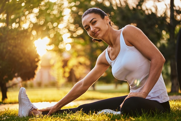 Jovem feliz que estica antes de correr ao ar livre. menina bonita esportes no parque está envolvida em fitness, aquecimento.