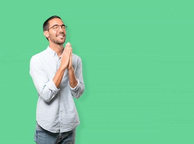 Jovem feliz rezando gesto