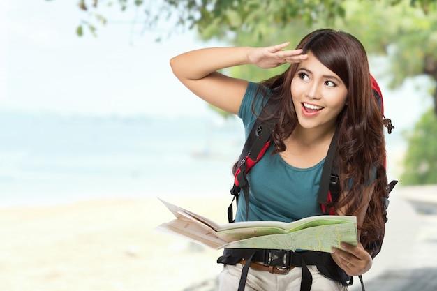 Jovem feliz saindo de férias com mochila e mapa
