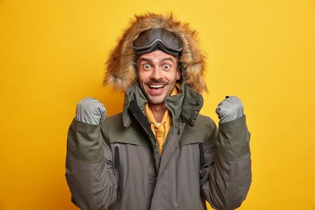 Jovem feliz se alegra com a chegada do inverno levanta os punhos cerrados, usa luvas e jaqueta quente com capuz